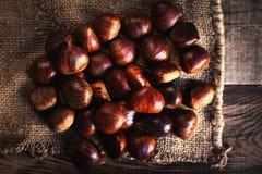 Châtaignes fraîches sur le sac brun de sac Grands écrous savoureux mûrs de coffre dessus Image stock