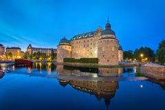Château d'Orebro se reflétant dans l'eau le soir, Suède photographie stock
