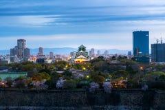 Château d'Osaka avec les fleurs de cerisier et le district des affaires à l'arrière-plan à Osaka, Japon image libre de droits