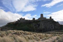 Château de Bamburgh dans le Northumberland à travers les dunes photo stock