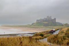 Château de Bamburgh et le marcheur de pluie photo libre de droits