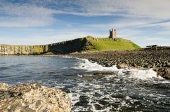 Château de Dunstanburgh avec la mer Image libre de droits