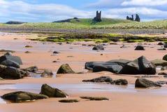 Château de Dunstanburgh de plage d'Embleston Photographie stock