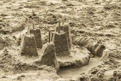 Château de sable de Childs fait à partir des moules avec des bâtons pour des drapeaux sur le dessus et un fossé abandonné sur la  photo stock