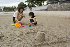 Château de sable de bâtiment de mère et de fille Photo stock
