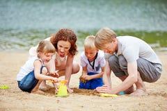 Château de sable de fondation d'une famille sur la plage photo stock