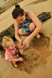 Château de sable de mère et de descendant Photo stock