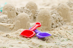Château de sable et les pelles et le râteau Images libres de droits