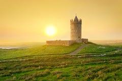 Château irlandais sur la côte au coucher du soleil Image stock