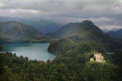 Château par le lac dans des crêtes de montagne de forêt Images stock