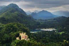 Château par le lac dans des crêtes de montagne de forêt Image stock