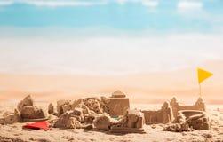 Châteaux de sable, tours et Colisé brisés de drapeaux sur la mer de fond Image libre de droits