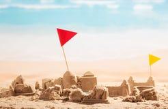 Châteaux de sable, tours et Colisé délabrés de drapeaux sur la mer de fond Photographie stock libre de droits