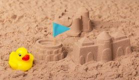 Châteaux et Colisé avec le drapeau, canard en caoutchouc en sable Photos libres de droits