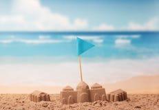 Châteaux faits de sable, drapeau bleu sur le fond de la mer Image stock