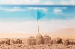 Châteaux faits en sable et drapeau sur la mer de fond Image libre de droits
