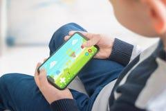 Chłopiec bawić się grę na jego telefonie Pojęcie nowożytna rozrywka dla dzieci zdjęcie royalty free