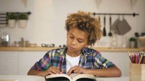 Chłopiec obsiadanie za stołową i czytelniczą książką zdjęcie wideo