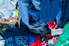 Chłopiec odzież reprezentuje ubraniową darowiznę, dzieciaka kreślarz, czyści w górę, stos odziewa, dezorganizacja i czyści u zdjęcia stock