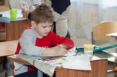 Chłopiec robi grafice przy szkolnym obsiadaniem przy jego biurkiem obraz royalty free