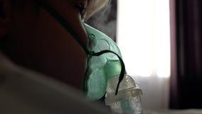 Chłopiec robi inhalacji w domu na łóżkowym naprzeciw okno zdjęcie wideo