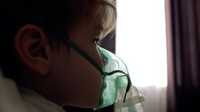 Chłopiec robi inhalacji w domu na łóżkowym naprzeciw okno zbiory