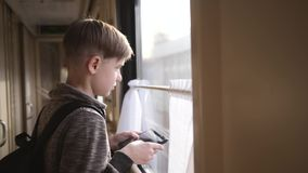 Chłopiec stojaki przy taborowym okno z pastylką w jego ręki wewnętrzna mknięcia pociągu podróż Urlopowa turystyka, podróżuje świa zbiory wideo