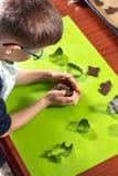 Chłopiec tworzy brązu tort z jego ręką i miażdży Przygotowani ciastka i drewniana toczna szpilka kłamają obok kontuaru obrazy royalty free