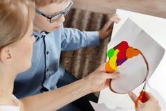 Chłopiec w błękitnej koszula z mum Chłopiec mamy cięć nożyce z plastikową pracą robić dzieckiem obrazy royalty free
