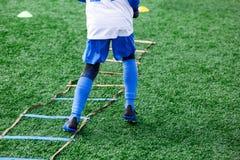 Chłopiec w białym białym sportswear bieg na boisku do piłki nożnej Młody futbolisty dribling Trenujący, aktywny styl życia, sport zdjęcie stock