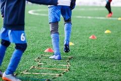 Chłopiec w białym sportswear bieg na boisku do piłki nożnej Młody futbolisty dribling Trenujący, aktywny styl życia, sport, dziec zdjęcie royalty free