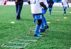 Chłopiec w białym sportswear bieg na boisku do piłki nożnej Młody futbolisty dribling Trenujący, aktywny styl życia, sport, dziec obrazy royalty free