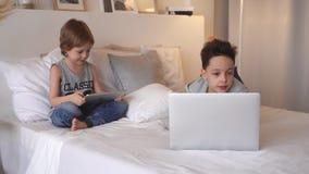 Chłopiec w rodzica ` łóżku przy rankiem z laptopem i pastylką Brat sztuki gry komputerowe Rodzeństwa i gadżety zbiory