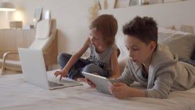 Chłopiec w rodzica ` łóżku przy rankiem z laptopem i pastylką Brat sztuki gry komputerowe Rodzeństwa i gadżety zdjęcie wideo