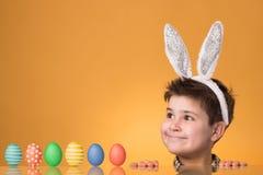 Chłopiec z ucho zając blisko stołu z malującymi jajkami fotografia royalty free