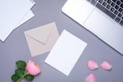 Chèque-cadeau avec la rose et l'ordinateur portable roses sur le fond gris photographie stock libre de droits
