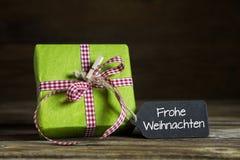 Chèque-cadeaux de la Navidad con el texto alemán en fondo de madera Fotografía de archivo libre de regalías