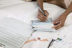 Chèque d'écriture de femme sur le lit par fin d'ordinateur portable de la vue courbe de mains Photo stock
