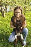 Chèvre de fille et de bébé dans le jardin fleuri images libres de droits