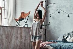 Ché mattina grande! Allungamento e smil attraenti della giovane donna Fotografia Stock Libera da Diritti