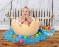 Chéri adorable s'asseyant en oeuf de pâques géant Images stock