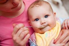 Chéri alimentante de mère Photo stock