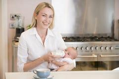 Chéri alimentante de mère avec le sourire de café Photos libres de droits