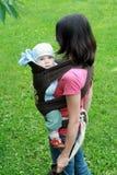 Chéri avec la maman dans le transporteur de chéri Image libre de droits