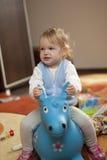 Chéri conduisant un cheval de jouet Photographie stock libre de droits