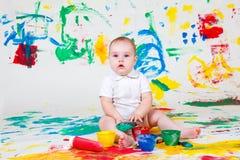Chéri curieuse jouant avec des peintures images libres de droits