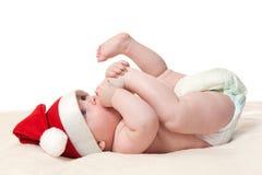 Chéri dans le chapeau de Noël jouant avec le pied Photographie stock