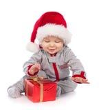 Chéri dans le chapeau de Santa jouant avec le cadre de cadeau de Noël Photos stock