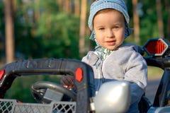 Chéri dans un véhicule de jouet Photographie stock libre de droits