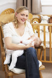 Chéri de allaitement de mère dans la pépinière Image libre de droits